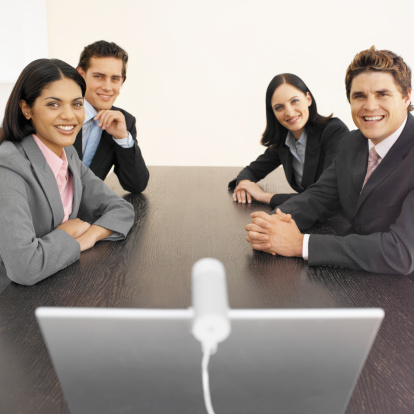 business executives in a meeting, using videoconferencing