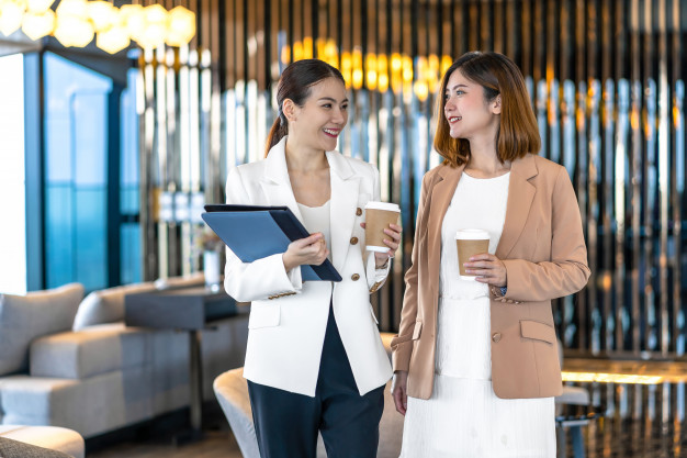 two-asian-businesswomen-talking-during-coffee-break-modern-office-coworking-space_41418-3673